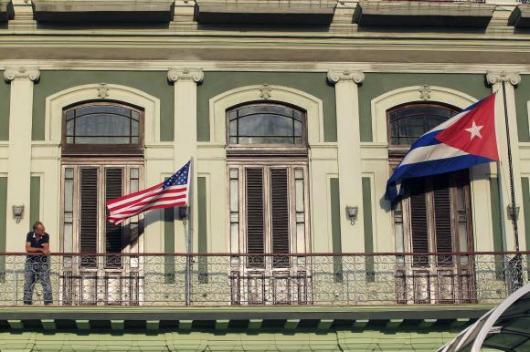 Man stands near national flags of U.S. and Cuba on balcony of a hotel being used by first U.S. congressional delegation to Cuba since change of policy announced by U.S. President Obama, in Havana