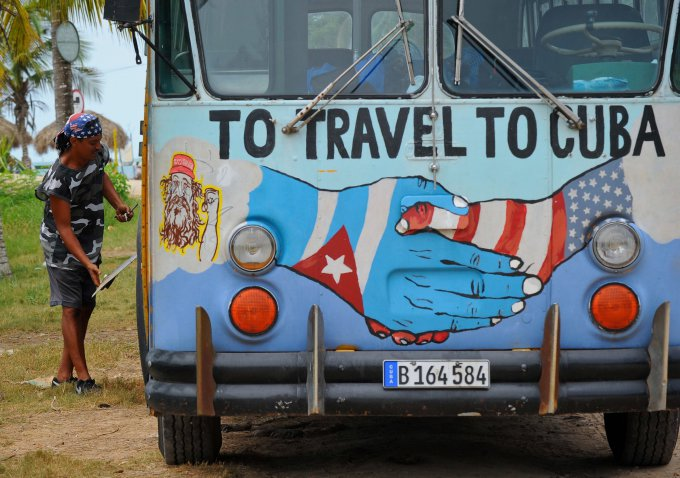 A bus with the Cuban and US flags is seen on a beach in Havana, on August 12, 2015. Cuba and the United States have restored full diplomatic relations last month after more than a half century of enmity. AFP PHOTO / YAMIL LAGE