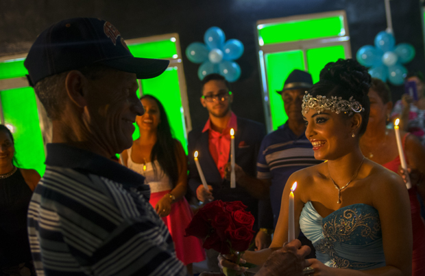 "In this Dec. 20, 2015 photo, Daniela Santos Torres, 15, gives a candle to her father as she gifts candles to the most important members of her family during her quinceanera party in the town of Punta Brava near Havana, Cuba. Daniela left Cuba when she was 3, returning in December for her quinceanera photos and party. She now lives in Glendale, Arizona, where her father runs a home remodeling business. She said returning to Cuba for her celebration was ""a dream,"" allowing her to include her extended family and friends on the island. (AP Photo/Ramon Espinosa)"