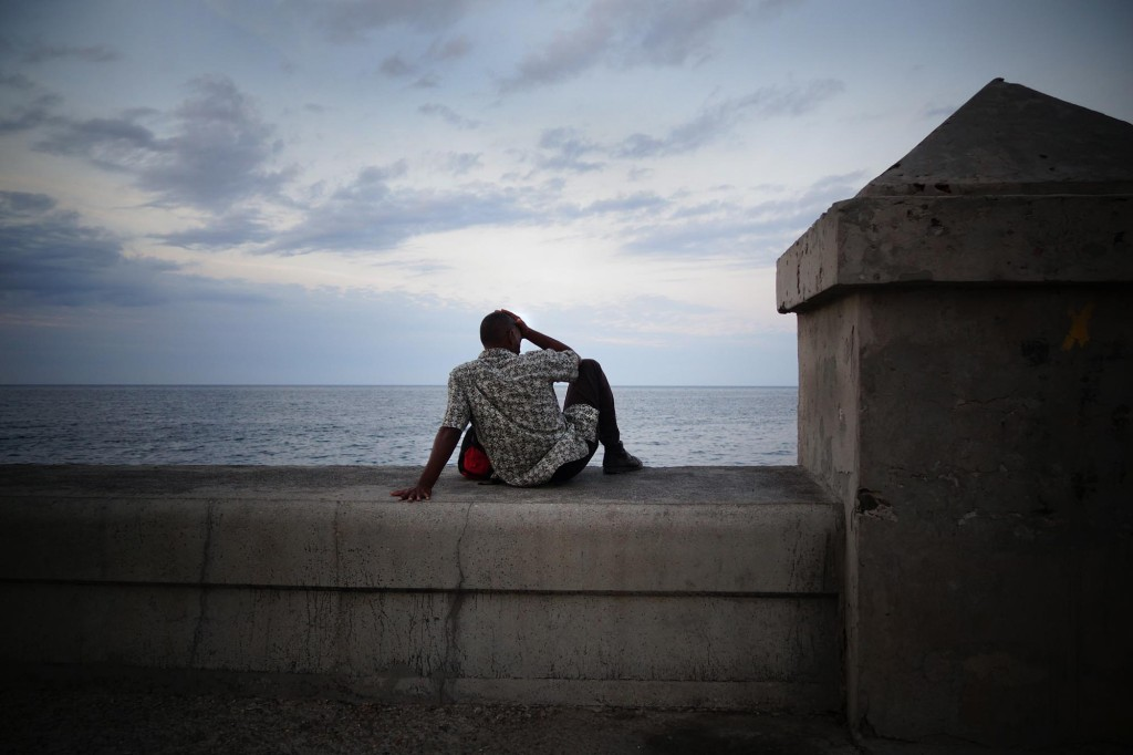 Malecon, the seaside corso in Havana. Most locals do not have money to go out to bars or restaurants - those are almost exclusively for tourists - so Habaneros spend their evenings sitting on the wall and looking at the sea.
