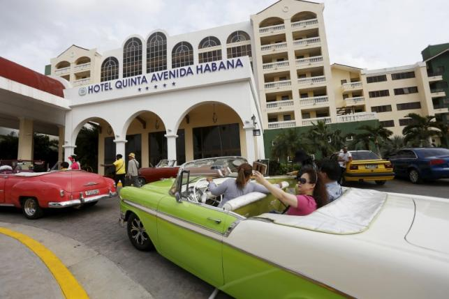 Tourists take a selfie while sitting in a vintage car outside the Quinta Avenida Habana Hotel in Havana, March 19, 2016. REUTERS/Stringer