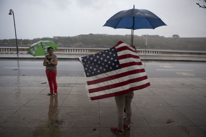 A Cuban man carrying the Stars and Stripes waits in the rain to wave to U.S. President Barack Obama's convoy as it arrives along the Malecon into Old Havana, Cuba, Sunday, March 20, 2016. Obama's trip is a crowning moment in his and Cuban President Raul Castro's ambitious effort to restore normal relations between their countries. (AP Photo/Rebecca Blackwell)