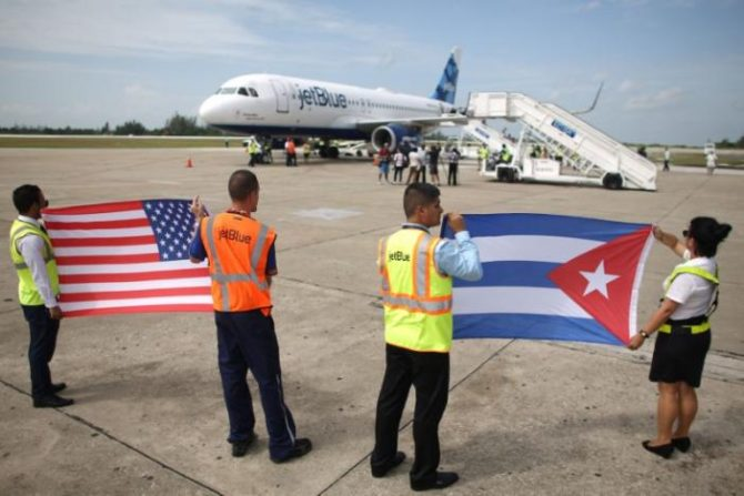 Ground crew hold U.S. and Cuban flags near a recently landed JetBlue aeroplane, the first commercial scheduled flight between the United States and Cuba in more than 50 years, at the Abel Santamaria International Airport in Santa Clara, Cuba, August 31, 2016. REUTERS/Alexandre Meneghini