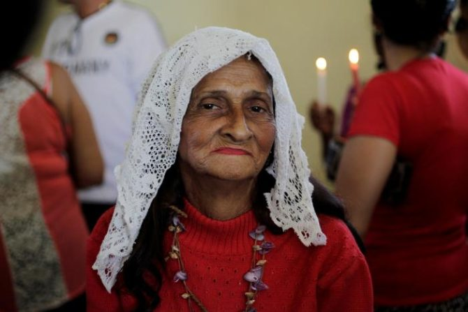 A woman attends a mass at the Saint Barbara Church where people gathered to pray on the day known as Santa Barbara to Catholics and Chango to followers of Cuba's Santeria religion, in Havana, Cuba, December 4, 2016. REUTERS/Stringer